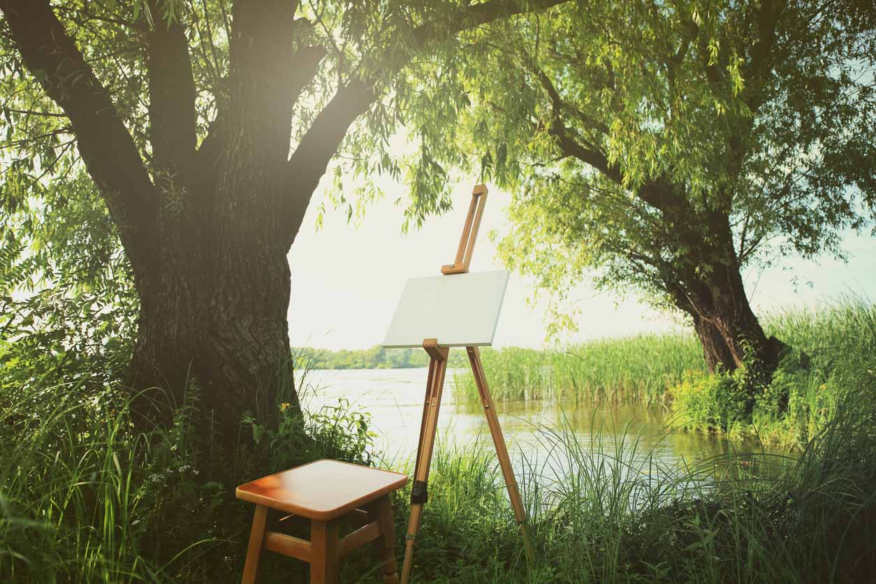 Blank canvas rests on a easel on lake landscape.